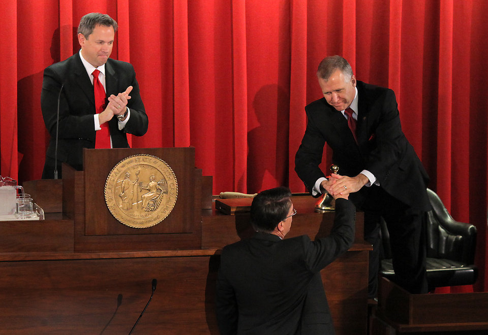 Photo - North Carolina Gov. Pat McCrory, bottom, shakes hands with Speaker of the House Thom Tillis, right, near Lt. Gov. Dan Forest, left, after McCrory delivered the State of the State address at the Legislative Building in Raleigh, N.C., Monday, Feb. 18, 2013. (AP Photo/Ted Richardson)
