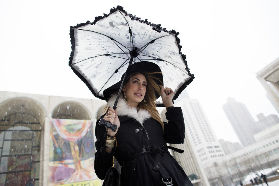 Photo - Lauren Rae Levy, of Manhattan, stands outside the Metropolitan Opera House in the snow at Lincoln Center during Fashion Week, Friday, Feb. 8, 2013, in New York. Snow began falling across the Northeast on Friday, ushering in what was predicted to be a huge, possibly historic blizzard and sending residents scurrying to stock up on food and gas up their cars. (AP Photo/John Minchillo)