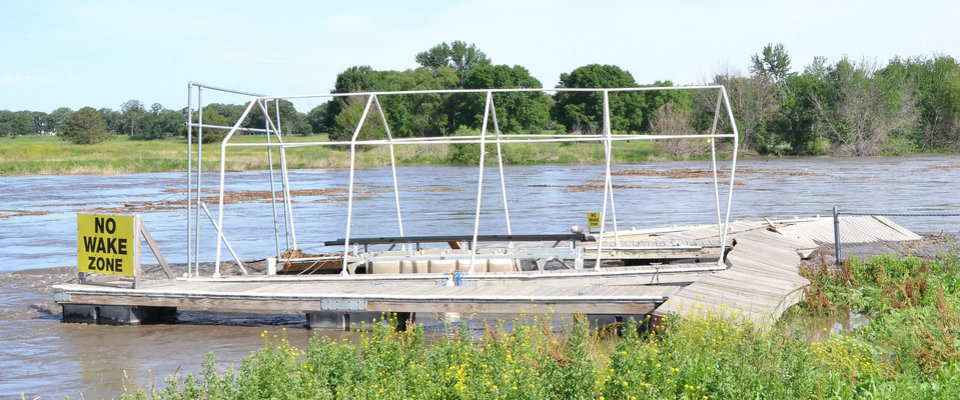 Photo - A boat dock that had broken loose and drifted a short distance downstream from the Missouri River Boat Club on the Big Sioux River in Sioux City, Iowa, is shown Thursday, June 19, 2014. Cities along the river were working to battle record flooding from the river. (AP Photo/Sioux City Journal, Tim Hynds)