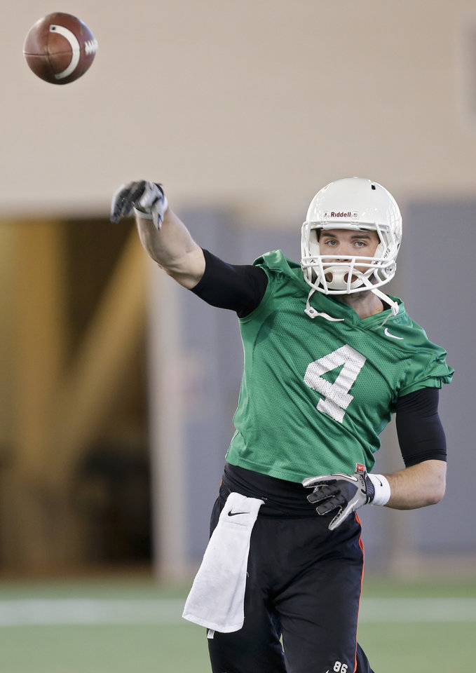 Photo - Oklahoma State quarterback J.W. Walsh throws a pass during the first day of spring football practice at Oklahoma State University in Stillwater, Okla., on Monday, March 10, 2014.  Photo by Chris Landsberger, The Oklahoman