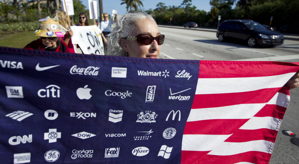 Photo -   Karen Levin, carrying an American flag with corporate logos, protests Wal-Mart in Boynton Beach, Fla., Friday, Nov 23, 2012. Wal-Mart employees and union supporters are taking part in today's nationwide demonstration for better pay and benefits A union-backed group called OUR Walmart, which includes former and current workers, was staging the demonstrations and walkouts at hundreds of stores on Black Friday, the day when retailers traditionally turn a profit for the year. (AP Photo/J Pat Carter)