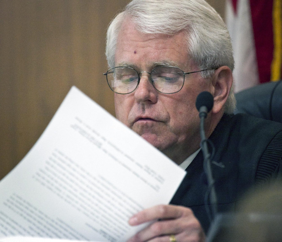 Photo -   Judge Clark Owens looks over papers during the preliminary hearing for Daniel U. Perez, in Sedgwick County District Court in Wichita, Kan., Thursday June 7, 2012. Perez, 52, the self-proclaimed leader of a Kansas commune that lived off life insurance payouts of its dead members has been ordered to stand trial on a charge of premeditated first-degree murder. (AP Photo/The Wichita Eagle, Mike Hutmacher)