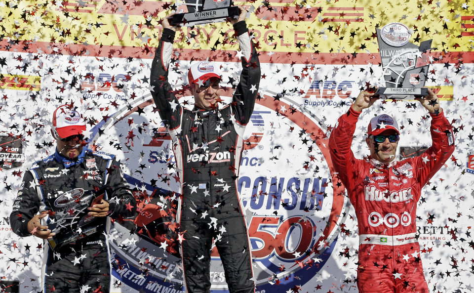 Photo - Winner Will Power is flanked by second place finisher Juan Pablo Montoya, left, and third place finisher Tony Kanaan after the Milwaukee Mile IndyCar auto race Sunday, Aug. 17, 2014, in West Allis, Wis. (AP Photo/Morry Gash)