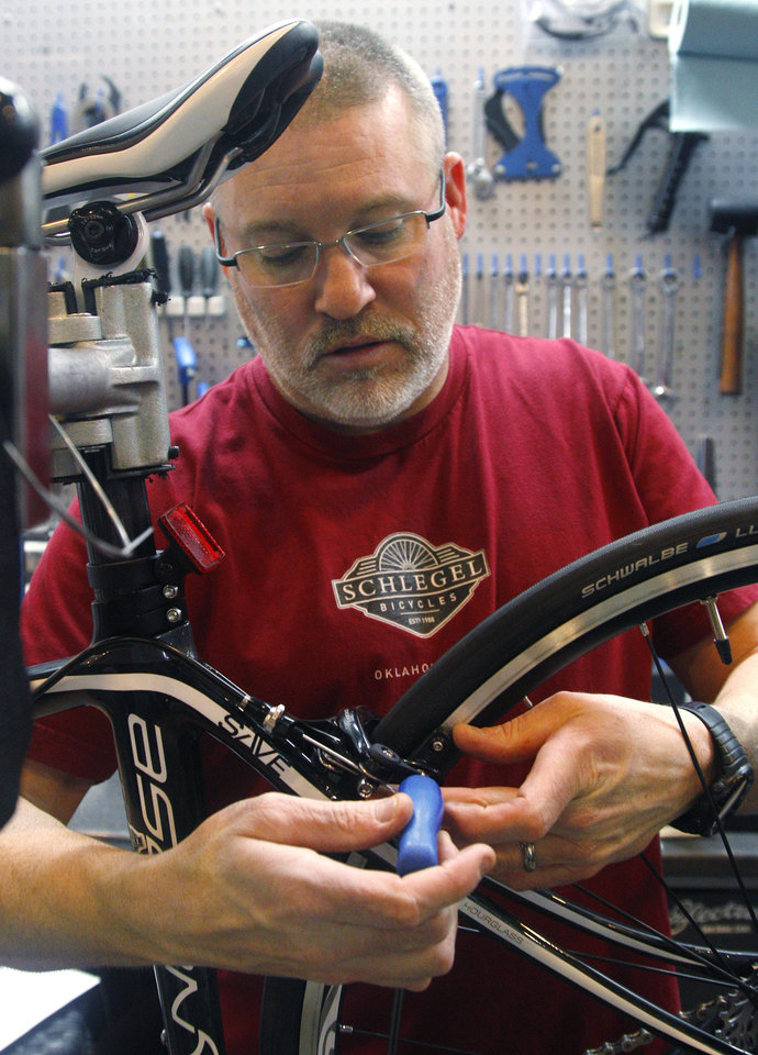 Photo -   Steve Schlegel, owner of Schlegel Bicycles, works on a bicycle in the shop's pro shop, in Oklahoma City, Thursday, Jan. 26, 2012. (AP Photo/Sue Ogrocki)