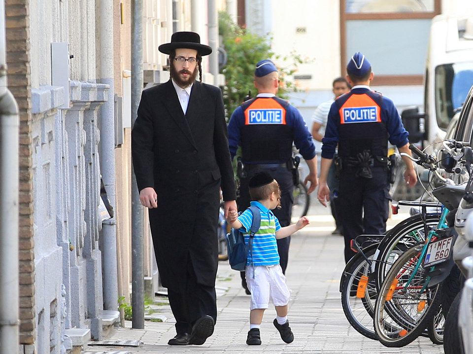 Photo - An orthodox Jew and a boy pass two police officers in Antwerp, Belgium, on Sunday, May 25, 2014. Police stepped up security at Jewish institutions, schools and synagogues after three people were killed and one seriously injured in a spree of gunfire at the Jewish Museum in Brussels on Saturday. (AP Photo/Yves Logghe)