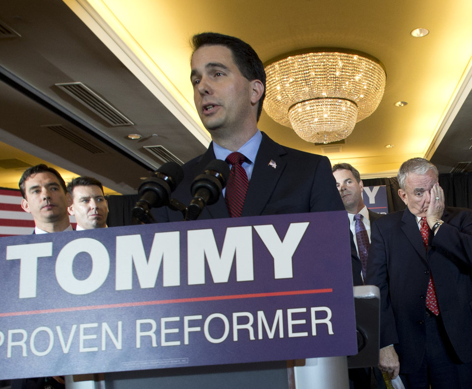 U.S. Senate candidate Tommy Thompson, right, waits to speak with supporters to concede the election Tuesday, Nov. 6, 2012 in Pewaukee, Wis. Speaking at the podium is Wisconsin Gov. Scott Walker. Thompson ran against Democratic challenger Tammy Baldwin who won the U.S. Senate seat vacated by Herb Kohl. (AP Photo/Jeffrey Phelps)
