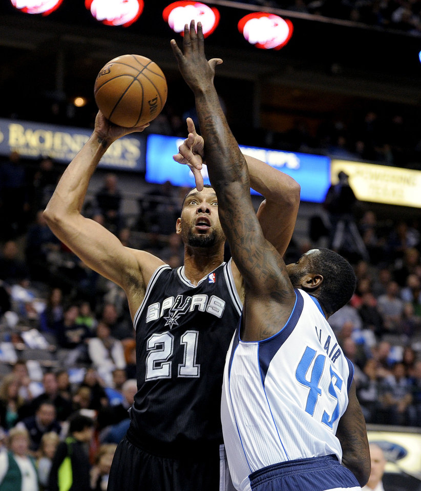 San Antonio Spurs forward Tim Duncan (21) shoots over Dallas Mavericks center DeJuan Blair (45) during the first half of an NBA basketball game, Thursday, Dec. 26, 2013, in Dallas. (AP Photo/Matt Strasen)
