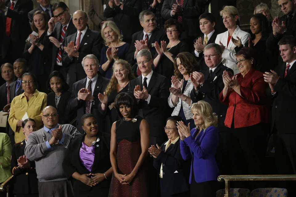 First lady Michelle Obama is applauded before President Barck Obama's State of the Union address during a joint session of Congress on Capitol Hill in Washington, Tuesday Feb. 12, 2013. Front row, from left are, Sgt. Sheena Adms, Nathaniel Pendleton, Cleopatra Cowley-Pendleton, Mrs, Obama, Menchu de Luna Sanchez and Jill Biden. Second row, third from left are, Oregon Gov. John Kitzhaber, Deb Carey and Apple CEO Tim Cook Amanda McMillian, Lt. Brian Murphy, (AP Photo/Pablo Martinez Monsivais) ORG XMIT: CAP113