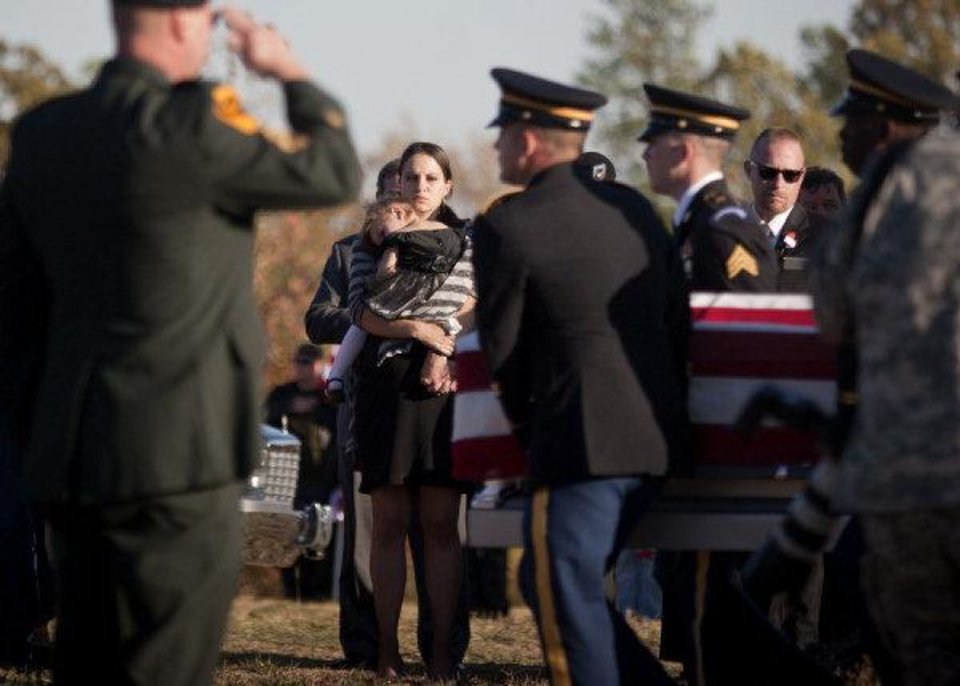 Family and friends of Spc. Sarina Butcher, 19, of Checotah, watch Friday as National Guard Honor Guard members carry her casket during a service at Friendship Cemetery in southwest Arkansas. PHOTO BY ADAM SACASA, THE TEXARKANA GAZETTE/AP