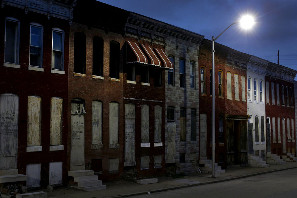 Photo - In this March 29, 2013 photo, vacant row houses line an empty street at dusk in Baltimore. The city has lost nearly a third of its population since it peaked in the 1950s, and today an estimated 16,000 buildings are vacant or abandoned. (AP Photo/Patrick Semansky)