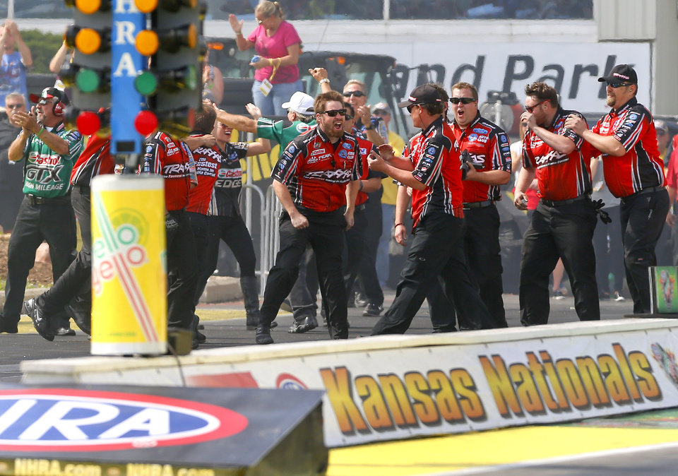 Photo - Funny Car driver Courtney Force's crew celebrates her championship run that gave her the 100th victory by a female driver in NHRA history at the NHRA Kansas Nationals drag races on Sunday, May 25, 2014, at Heartland Park in Topeka, Kan. (AP Photo/Topeka Capital-Journal, Chris Neal)