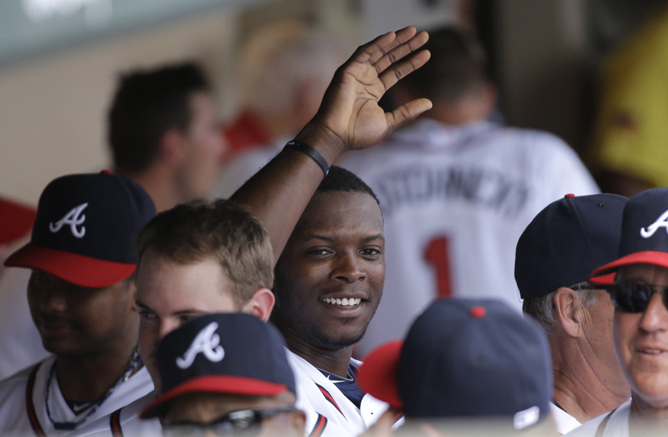 Photo - Atlanta Braves' Justin Upton is congratulated in the dugout after hitting a home run against the Miami Marlins during the fourth inning of an exhibition spring training baseball game Monday, Feb. 25, 2013, in Kissimmee, Fla. (AP Photo/David J. Phillip)