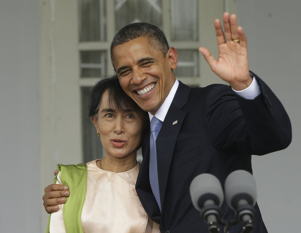 Photo -   U.S. President Barack Obama, right, waves as he embraces Myanmar democracy activist Aung San Suu Kyi after addressing members of the media at Suu Kyi's residence in Yangon, Myanmar, Monday, Nov. 19, 2012. Obama touched down Monday morning, becoming the first U.S. president to visit the Asian nation also known as Burma. (AP Photo/Pablo Martinez Monsivais)