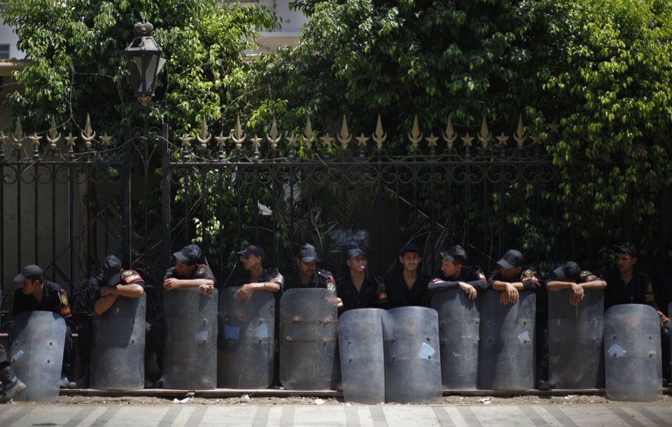 Egyptian riot police stand sit in the shade as they guard outside the parliament building in Cairo, Egypt, Tuesday, July 10, 2012. Egypt's Islamist-dominated parliament convened Tuesday in defiance of a ruling by the country's highest court and swiftly voted to seek a legal opinion on the decision that invalidated the chamber over apparent election irregularities. (AP Photo/Khalil Hamra) ORG XMIT: KH103