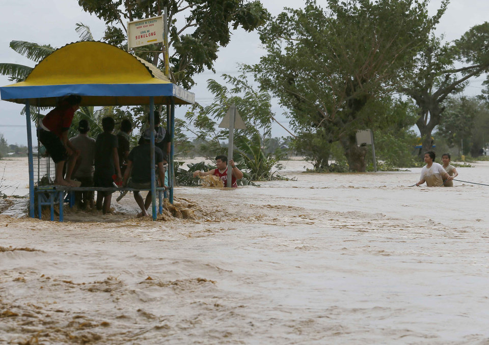 Photo - Residents wade through raging floodwaters brought about by Typhoon Koppu at Zaragosa township Nueva Ecija province, north of Manila, Philippines Monday, Oct. 19, 2015. Slow-moving Typhoon Koppu blew ashore with fierce wind in the northeastern Philippines early Sunday, toppling trees and knocking out power and communications and forcing the evacuation of thousands of villagers.(AP Photo/Bullit Marquez)