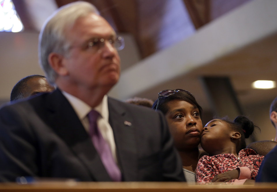 Photo - Sierra Smith sits with her 4-year-old daughter, Aniya, behind Missouri Gov. Jay Nixon, left, as they listen during a meeting of clergy and community members, Thursday, Aug. 14, 2014, in Florissant, Mo. Nixon says