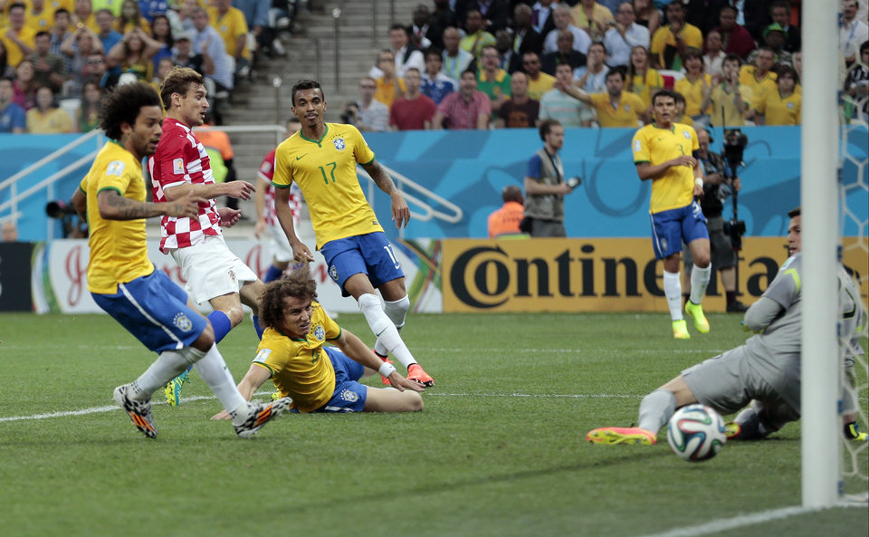 Photo - Brazil's Marcelo, left, scores on his own goal past Brazil's goalkeeper Jefferson while trying to clear the ball during the group A World Cup soccer match between Brazil and Croatia, the opening game of the tournament, in the Itaquerao Stadium in Sao Paulo, Brazil, Thursday, June 12, 2014.  (AP Photo/Ivan Sekretarev)