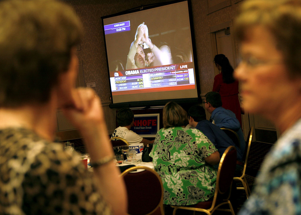 Photo - People at the Oklahoma City Republican Watch Party turn away from good news for state republicans to see the announcement that Barack Obama has been elected the next President of the United States during the Republican watch party at the Oklahoma City Marriott on Northwest Expressway in oklahoma City on Tuesday Nov. 4, 2008. By John Clanton, The Oklahoman