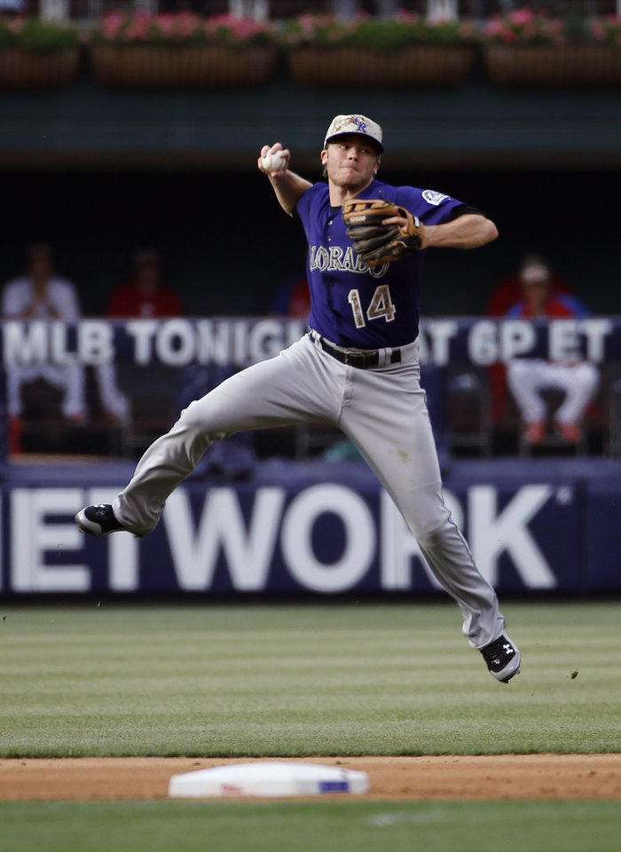 Photo - Colorado Rockies second baseman Josh Rutledge leaps to make a throw to first base on a single by Philadelphia Phillies' Chase Utley during the fourth inning of a baseball game, Monday, May 26, 2014, in Philadelphia. (AP Photo/Matt Slocum)