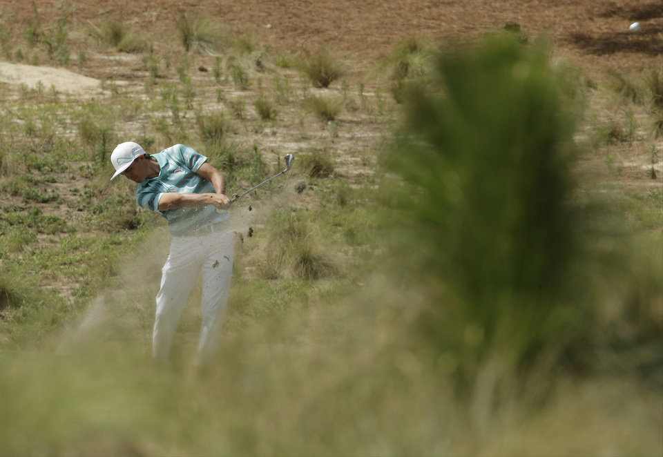 Photo - Rickie Fowler hits from the natural area on the eighth hole during the third round of the U.S. Open golf tournament in Pinehurst, N.C., Saturday, June 14, 2014. (AP Photo/Charlie Riedel)