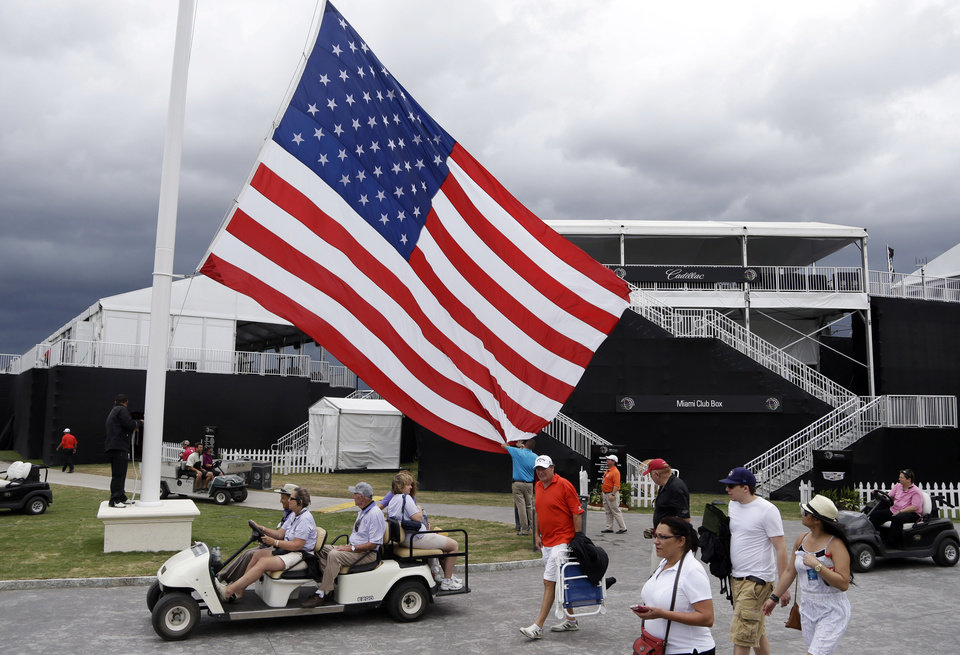 Photo - An American flag is lowered from a flag pole after play was suspended due to approaching inclement weather during the first round of the Cadillac Championship golf tournament, Thursday, March 6, 2014, in Doral, Fla. (AP Photo/Lynne Sladky)