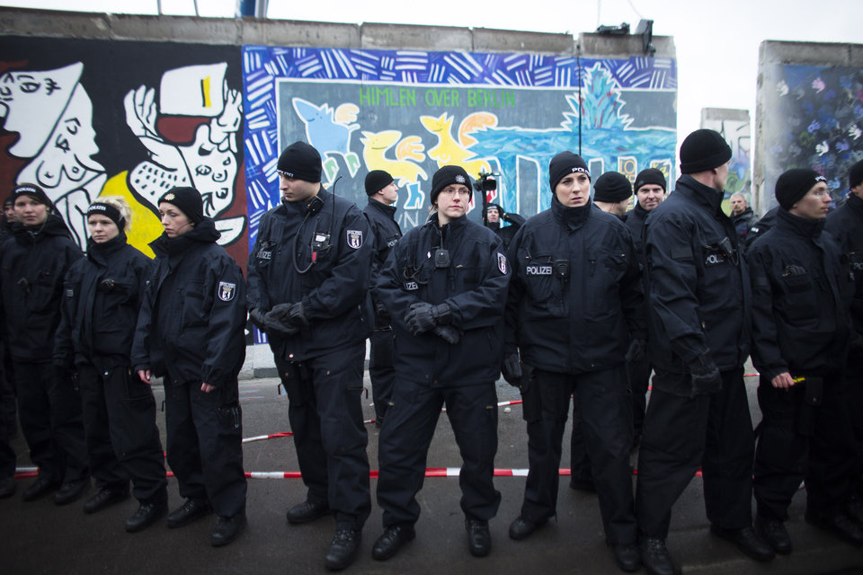 Photo - German police officers protect a part of the former Berlin Wall in Berlin, Germany, Friday, March 1, 2013. Berliners are protesting as a construction company removes a section of a historic stretch of the Berlin Wall known as the East Side Gallery to provide access to a riverside plot where luxury condominiums are being built. Since German reunification, the stretch of the wall has been preserved as a historical monument and transformed into an open air gallery painted with colorful murals, and has become a popular tourist attraction. (AP Photo/Markus Schreiber)