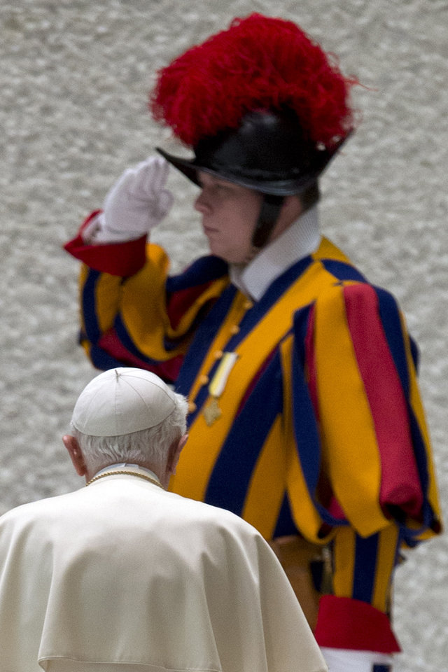 Photo - A Swiss Guard salutes as Pope Benedict XVI leaves at the end of his weekly general audience in the Paul IV hall at the Vatican, Wednesday, Jan. 2, 2013. (AP Photo/Andrew Medichini)