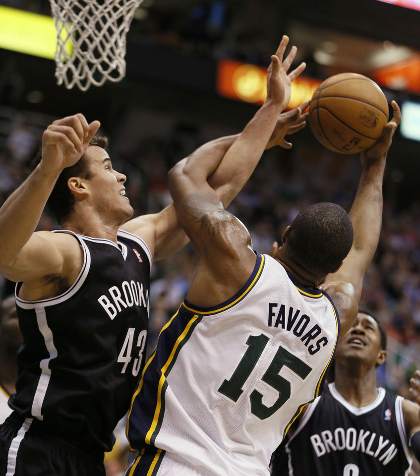 Brooklyn Nets\' Kris Humphries, left, fight for a rebound with Utah Jazz\'s Derrick Favors during the first half of an NBA basketball game, Saturday, March 30, 2013, in Salt Lake City. (AP Photo/George Frey)