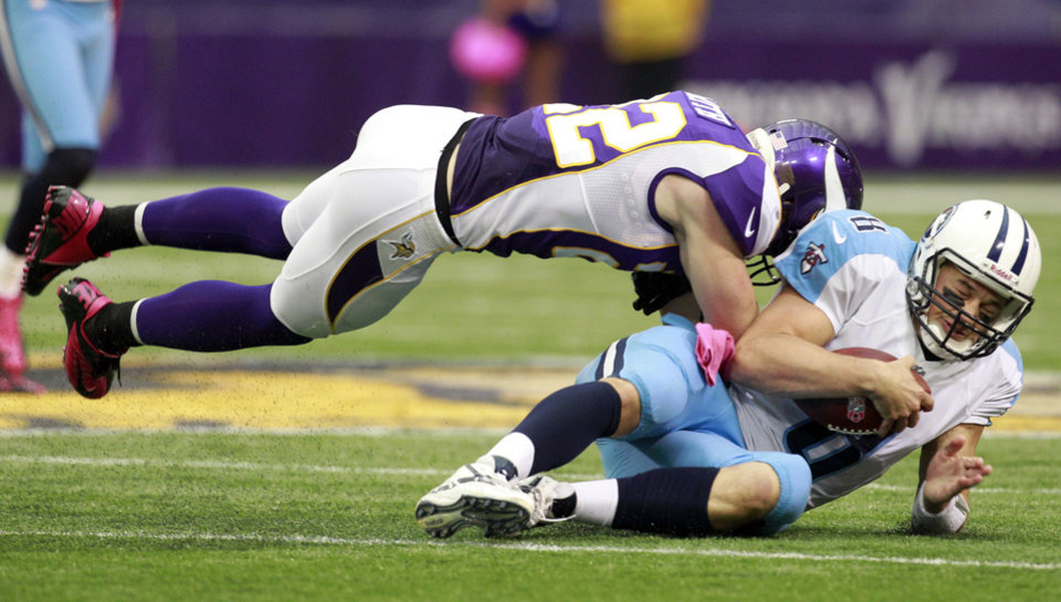 Tennessee Titans quarterback Matt Hasselbeck, right, is tackled by Minnesota Vikings safety Harrison Smith during the first half of an NFL football game on Sunday, Oct. 7, 2012, in Minneapolis. (AP Photo/Genevieve Ross)