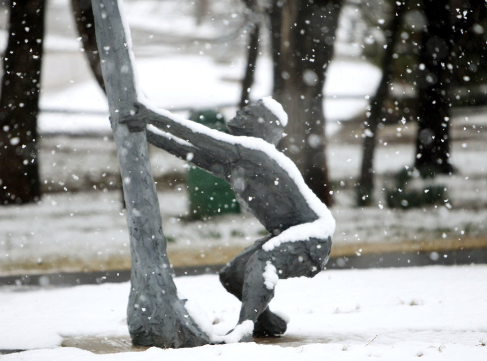 Photo - A bronze statue is piled with snow at Hafer Park in Edmond, OK, Tuesday, February 12, 2013,  By Paul Hellstern, The Oklahoman