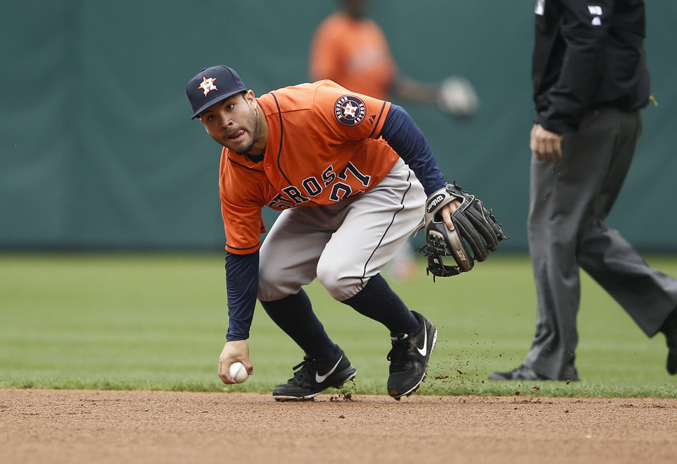 Photo - Houston Astros second baseman Jose Altuve picks up the grounder by Texas Rangers' Shin-Soo Choo during the first inning of a baseball game, Sunday, April 13, 2014, in Arlington, Texas. Shin-Soo Choo was called safe, but was ruled out after a challenge. (AP Photo/Jim Cowsert)