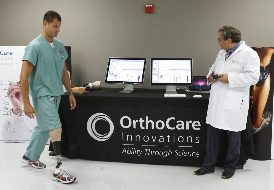 Photo - Michael Varro, left, prosthetist and amputee, demonstrates the Smart Pyramid and Compass on his prosthetic leg along with Dr. David Boone, OrthoCare Innovations Chief Technology Officer, at an OrthoCare Innovations press conference held in 2009.   PAUL B. SOUTHERLAND - PAUL B. SOUTHERLAND