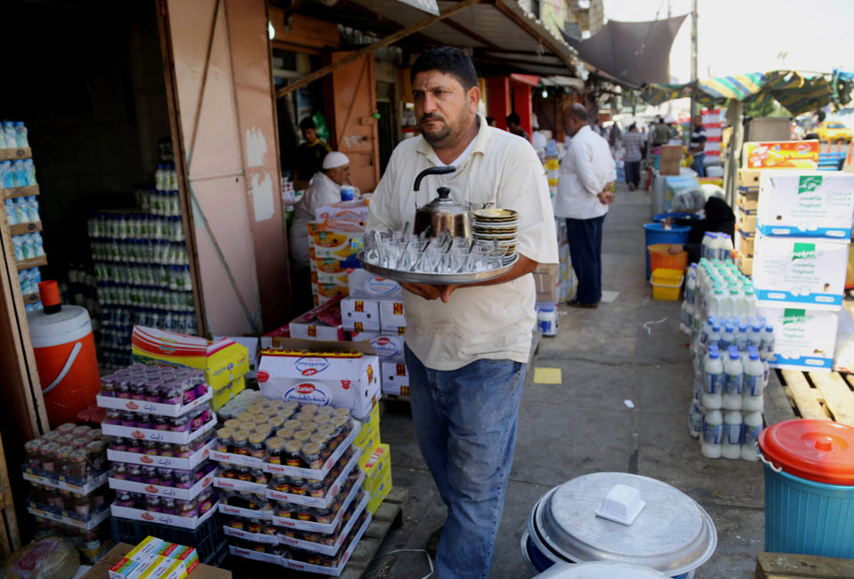 Photo - An Iraqi street tea vendor looks for customers at a market in Basra, Iraq's second-largest city, 340 miles (550 kilometers) southeast of Baghdad, Iraq, Thursday, June 19, 2014. Since June 6, Sunni fighters led by an al-Qaida breakaway group, the Islamic State of Iraq and the Levant, have swept through Iraq, seizing the second largest city, Mosul and Saddam Hussein's hometown of Tikrit as thousands of Iraqi soldiers melted away. The insurgents are now pressing to Baghdad. (AP Photo/ Nabil Al-Jurani)