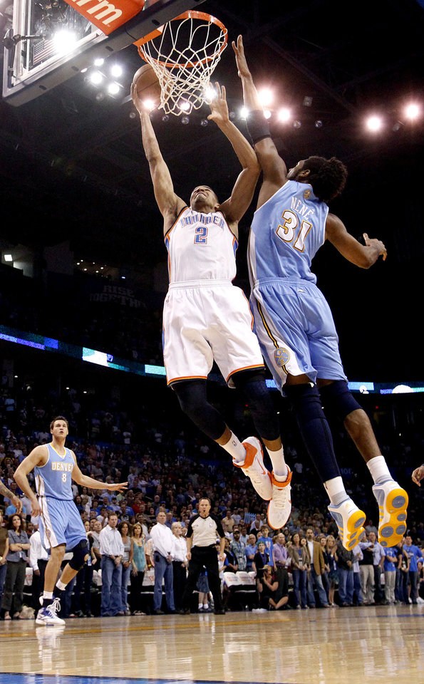 Photo - Oklahoma City's Thabo Sefolosha (2) shoots as Denver's Nene (31) defends during the NBA basketball game between the Oklahoma City Thunder and the Denver Nuggets, Friday, April 8, 2011, at the Oklahoma City Arena.. Photo by Sarah Phipps, The Oklahoman