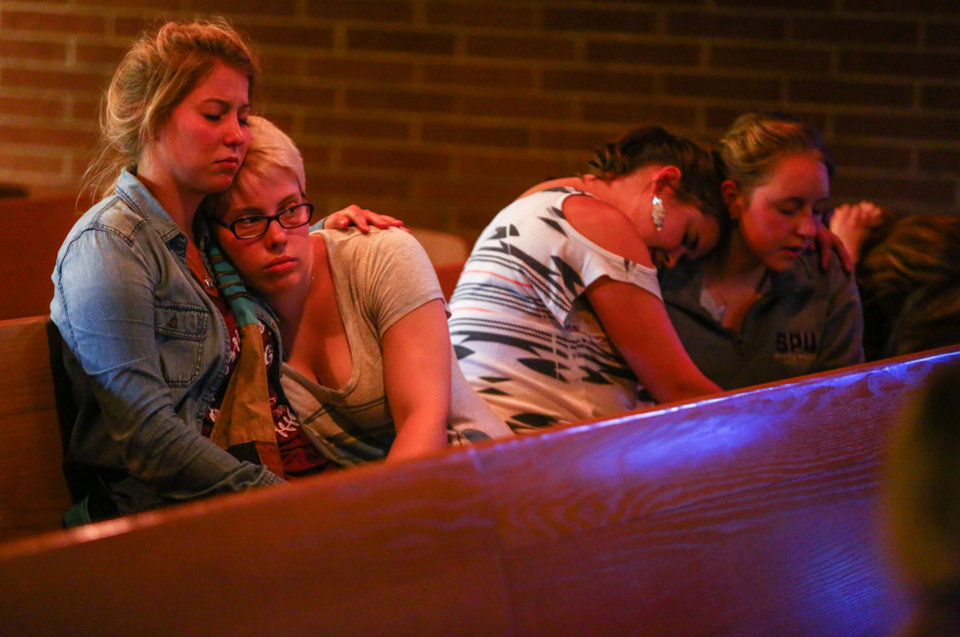 Photo - Annalyse Hurd, left, and Olivia Hutton, center, pray at the First Free Methodist Church after a shooting at Seattle Pacific University on Thursday, June 5, 2014. A man that shot students was disarmed by others at the scene. (AP Photo/seattlepi.com, Joshua Trujillo)