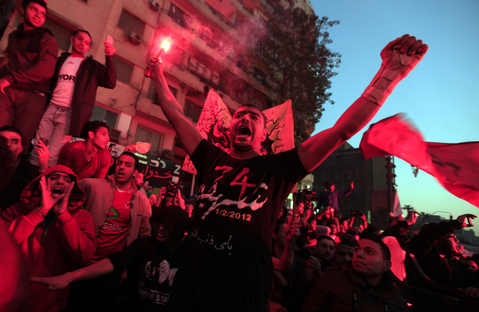 An Egyptian protester waves a flare during a rally of thousands of soccer fans of Egypt\'s most popular team, Al-Ahly, in Tahrir Square, the focal point of Egyptian uprising, in Cairo, Egypt, Friday, Jan. 18, 2013. Fans called for revenge a week before a court verdict is expected over last year\'s Port Said football stadium disaster, which killed 72 fans. (AP Photo/Khalil Hamra)