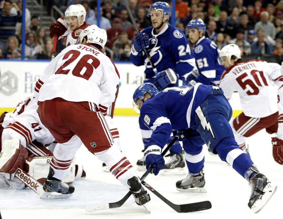 Photo - Tampa Bay Lightning left wing Ondrej Palat, of the Czech Republic, shoots the puck past Phoenix Coyotes goalie Mike Smith (41) and defenseman Michael Stone (26) for a goal after taking a pass from Lightning's Ryan Callahan (24) during the second period of an NHL hockey game, Monday, March 10, 2014, in Tampa, Fla. (AP Photo/Chris O'Meara)
