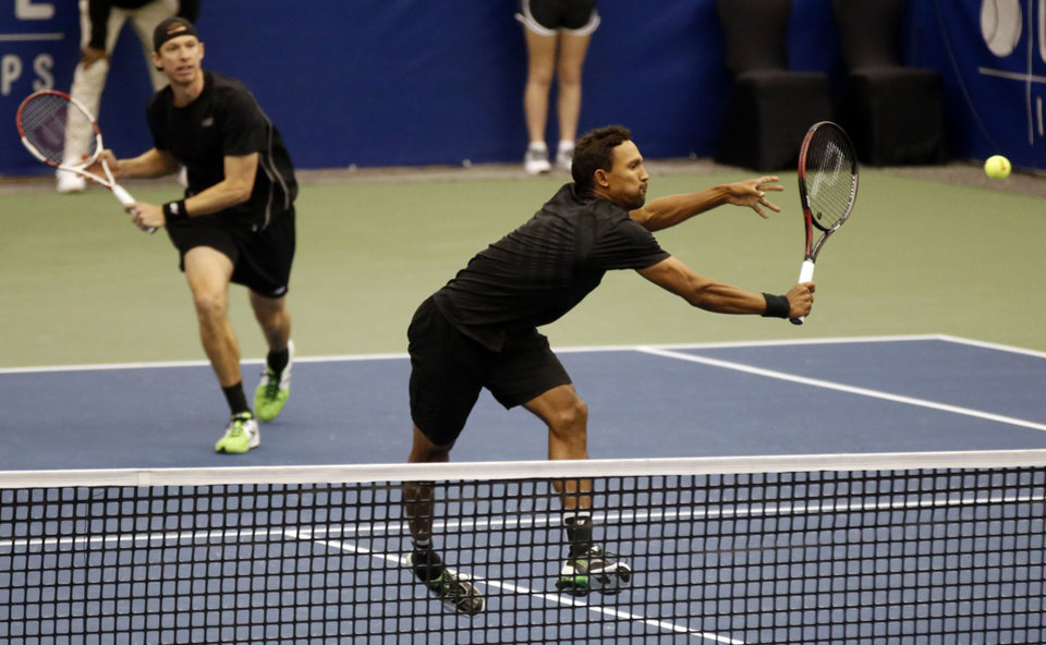 Photo - Raven Klaasen, front, of South Africa, returns to Mike and Bob Bryan as Eric Butorac watches in the finals at the U.S. National Indoor Tennis Championships, Sunday, Feb. 16, 2014 in Memphis, Tenn. Klaasen and Butorac won 6-4, 6-4. (AP Photo/Rogelio V. Solis)