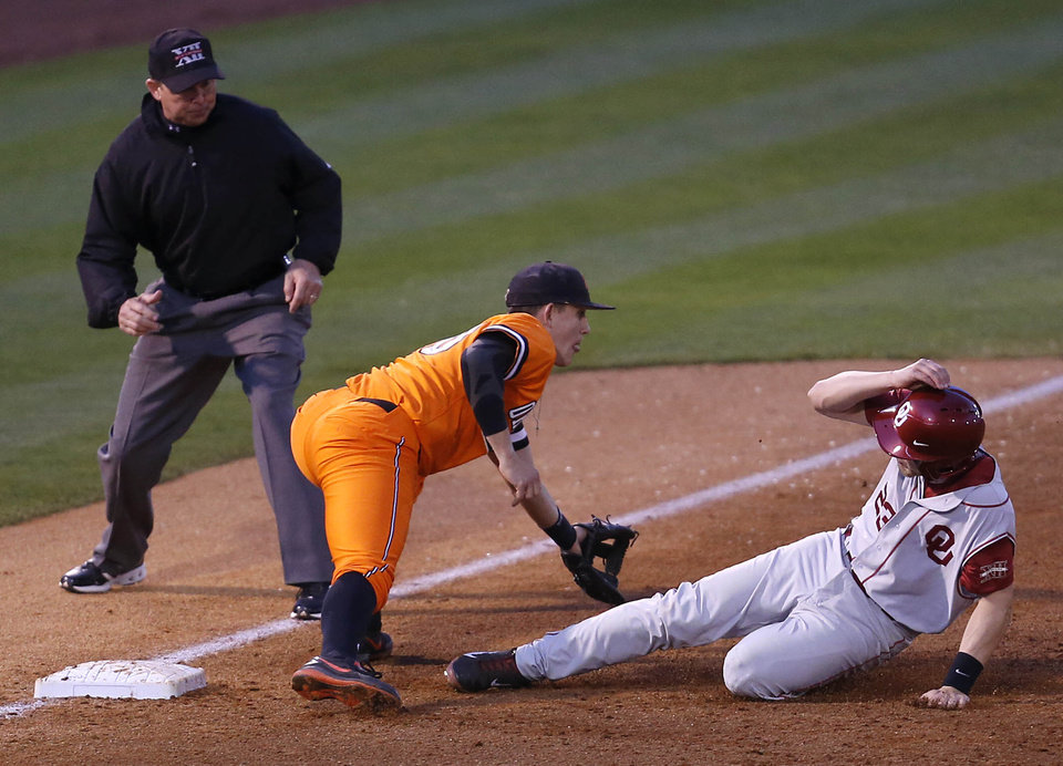 Oklahoma's Kolbey Carpenter slides into third base as Oklahoma State's Carig McConaughy waits for the throw during a Bedlam baseball game Saturday in Tulsa.                     Photo By Matt Barnard, The Tulsa World