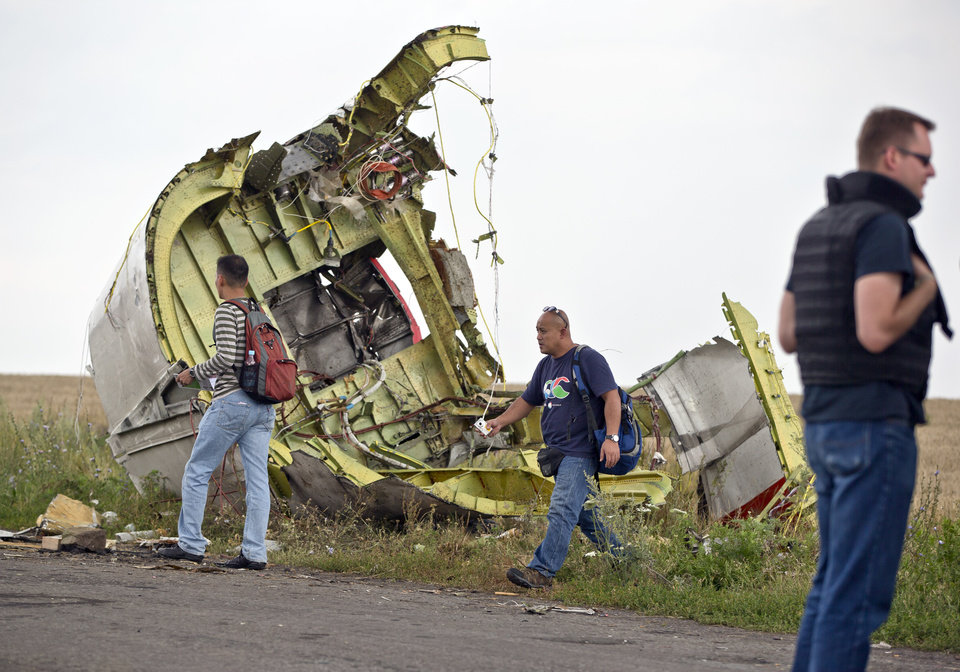 Photo - Malaysian air crash investigators walk by wreckage at the crash site of Malaysia Airlines Flight 17 near the village of Hrabove, eastern Ukraine, Tuesday, July 22, 2014. A team of Malaysian investigators visited the site along with members of the OSCE mission in Ukraine for the first time since the air crash last week.(AP Photo/Vadim Ghirda)