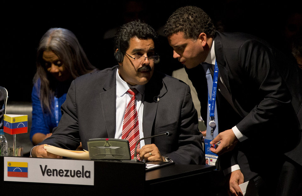 Venezuela\'s Vice President Nicolas Maduro, left, speaks and a member of his delegation speak during the closing ceremony of the CELAC-EU summit in Santiago, Chile, Sunday, Jan. 27, 2013. A 60-nation summit wrapped up in Chile on Sunday with leaders from the European Union, Latin America and the Caribbean renewing calls for giving investors