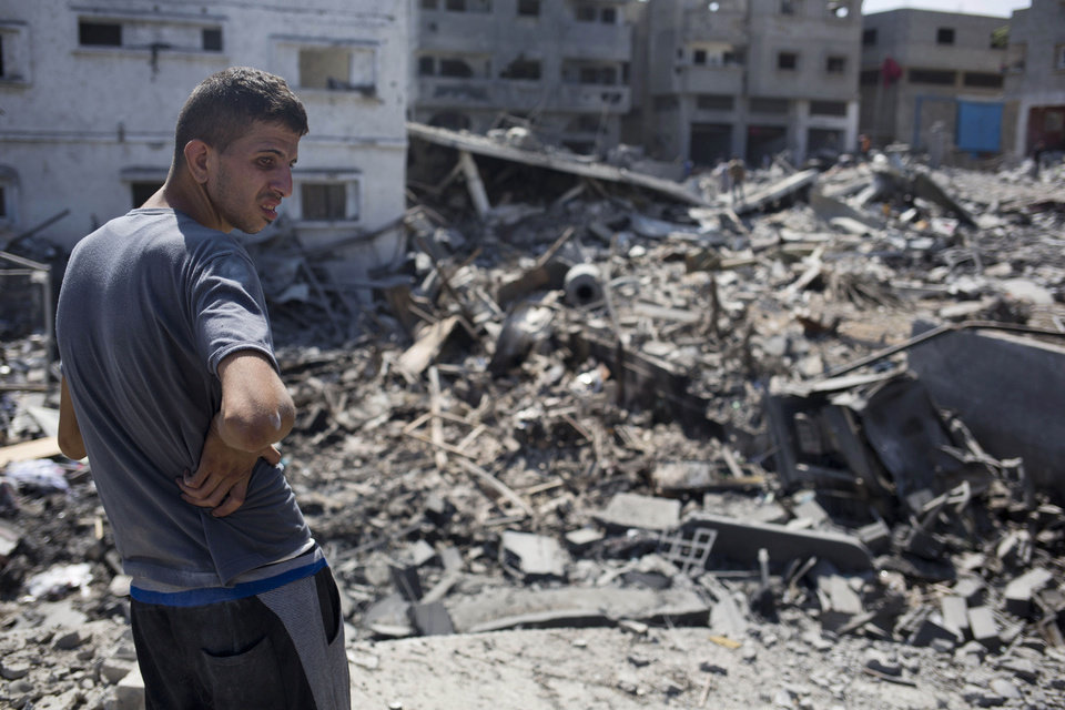 Photo - A Palestinian inspects a destroyed house in the heavily bombed Gaza City neighborhood of Shijaiyah, close to the Israeli border, Friday, Aug. 1, 2014. A three-day Gaza cease-fire that began Friday quickly unraveled, with Israel and Hamas accusing each other of violating the truce as several Palestinians were killed in a heavy exchange of fire in the southern town of Rafah. (AP Photo/Dusan Vranic)