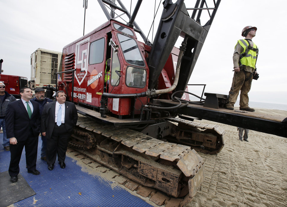 Photo - Belmar Mayor Matt Doherty, left, and New Jersey Gov. Chris Christie watch Wednesday, Jan. 9, 2013, in Belmar, N.J., as a piledriver machine drives-in the first piling to begin Belmar's construction on a 1.3-mile boardwalk to replace the walkway destroyed by Superstorm Sandy in October. Mayor Doherty says new designs including the use of strong hurricane tie-down straps will help anchor the new boardwalk to its support moorings. The town intended to rebuild the boardwalk with tropical rain forest wood but abandoned those plans Tuesday, saying it wanted to avoid a protracted legal battle with environmentalists. (AP Photo/Mel Evans)