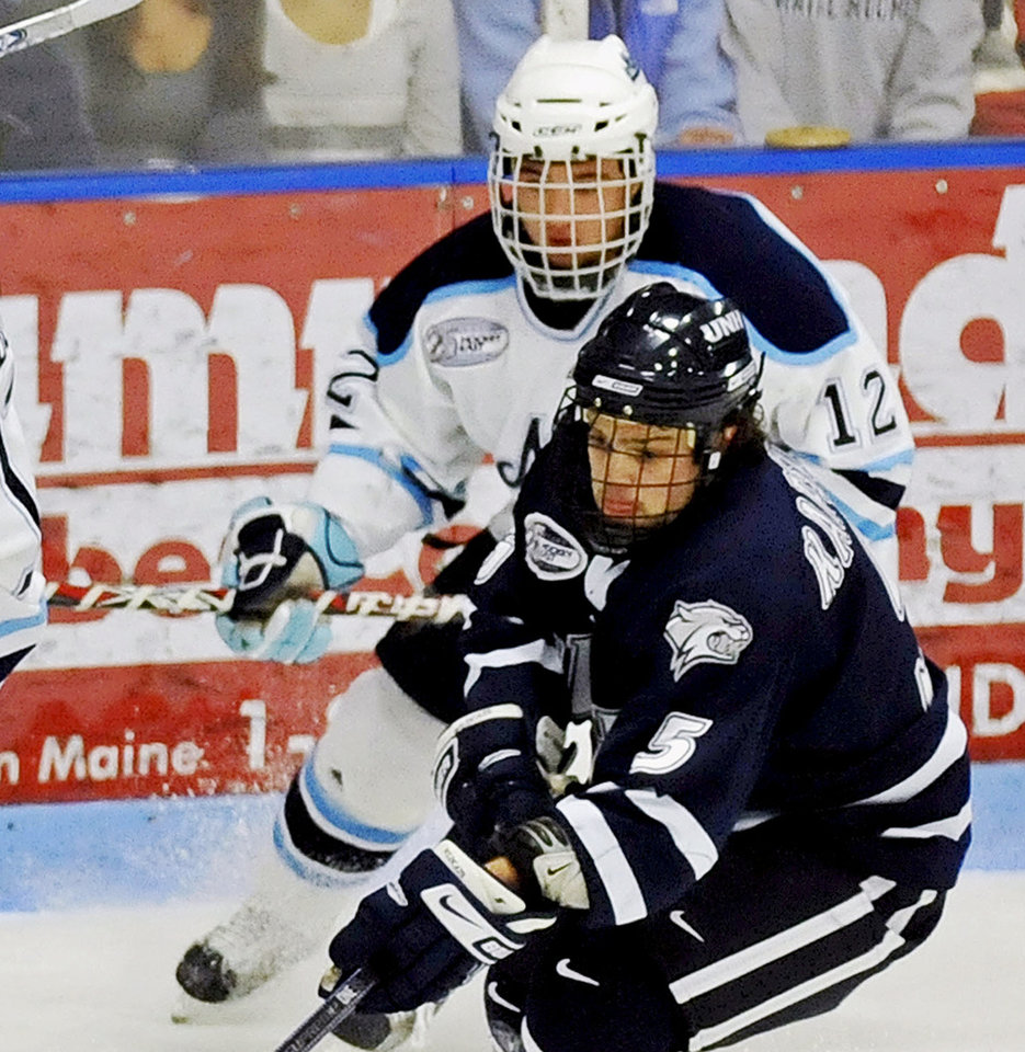 Photo - FILE - In this Jan. 4, 2009 file photo, Maine's Kyle Solomon (12) chases after New Hampshire's Kevin Kapstad, (5) during an NCAA college hockey game in Orono, Maine. Solomon is one of the plaintiffs in a class-action head injury lawsuit working its way through federal court in Chicago. The NCAA and the plaintiffs announced a settlement on Tuesday, July 29, 2014.  (AP Photo/Michael C. York, File)