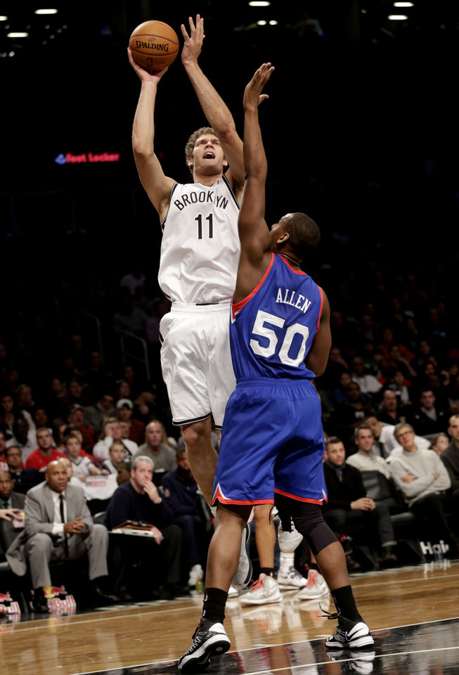 Brooklyn Nets\' Brook Lopez, top, takes a shot over Philadelphia 76ers\' Lavoy Allen during the first half of the NBA basketball game at the Barclays Center Sunday, Dec. 23, 2012 in New York. (AP Photo/Seth Wenig)