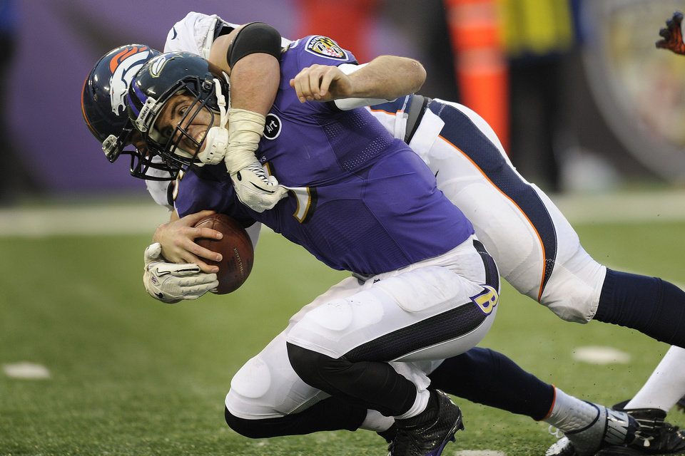 Photo - Baltimore Ravens quarterback Joe Flacco is sacked by Denver Broncos defensive end Derek Wolfe during the second half of an NFL football game in Baltimore, Sunday, Dec. 16, 2012. The Broncos defeated the Ravens 34-17. (AP Photo/Nick Wass)
