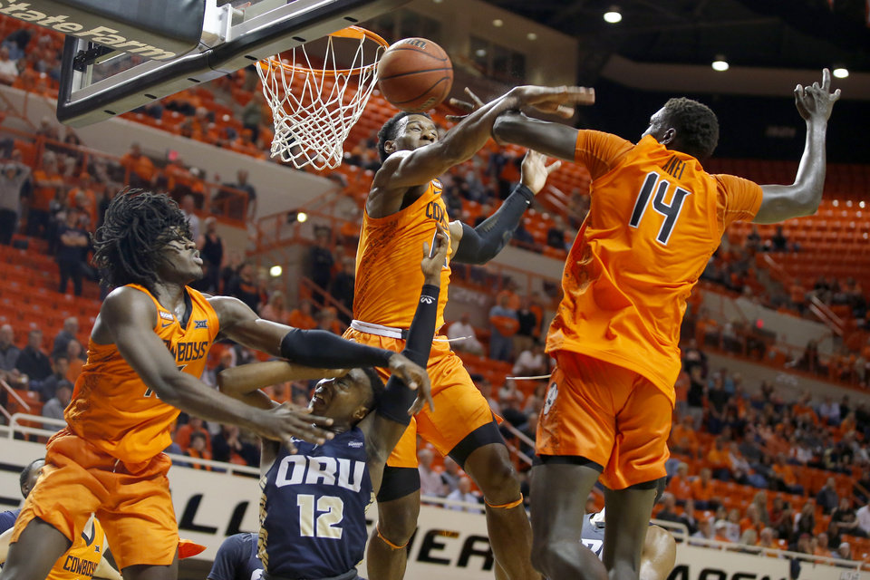 Photo - R.J. Fuqua (12) of Oral Roberts is fouled as he tries to go to the basket between Oklahoma State's Isaac Likekele (13), Cameron McGriff (12) and Yor Anei (14) during an NCAA basketball game between the Oklahoma State University Cowboys (OSU) and the Oral Roberts Golden Eagles (ORU) at Gallagher-Iba Arena in Stillwater, Okla., Wednesday, Nov. 6, 2019. Oklahoma State won 80-75. [Bryan Terry/The Oklahoman]