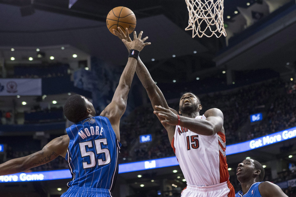 Photo - Orlando Magic's E'Twaun Moore, left, blocks Toronto Raptors' Amir Johnson's shot during the first half of an NBA basketball game in Toronto, Sunday, Feb. 23 , 2014. (AP Photo/The Canadian Press, Chris Young)