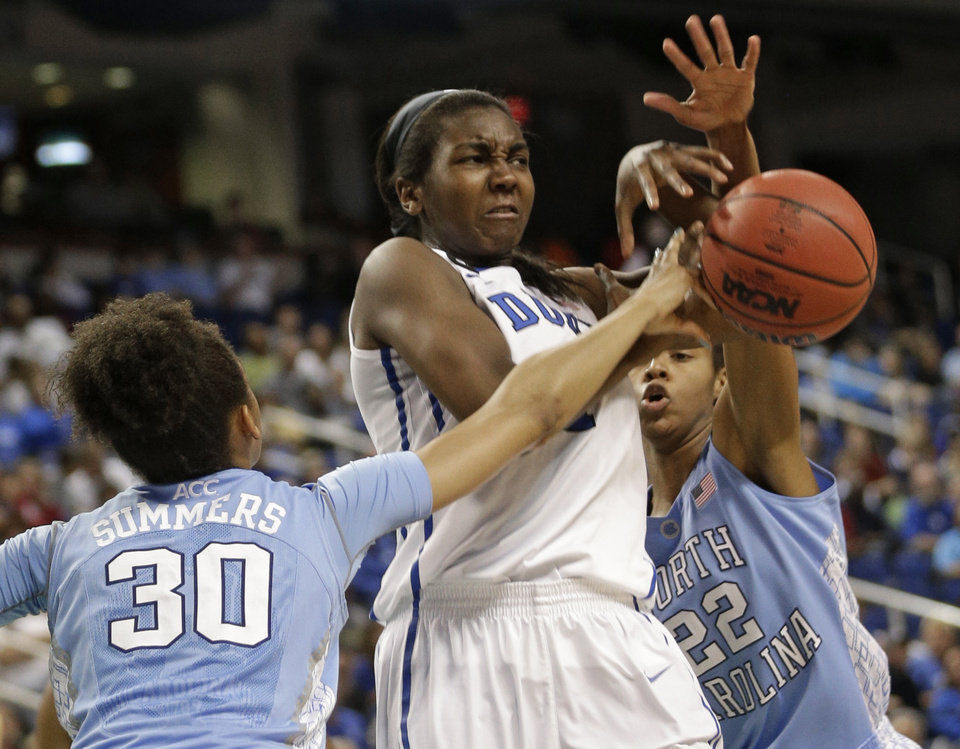 Photo - Duke's Elizabeth Williams, center, is fouled as she tries to shoot between  North Carolina's Hillary Summers, left, and N'Dea Bryant, right, during the first half of an NCAA college basketball semi-final game at the Atlantic Coast Conference tournament in Greensboro, N.C., Saturday, March 8, 2014. (AP Photo/Chuck Burton)