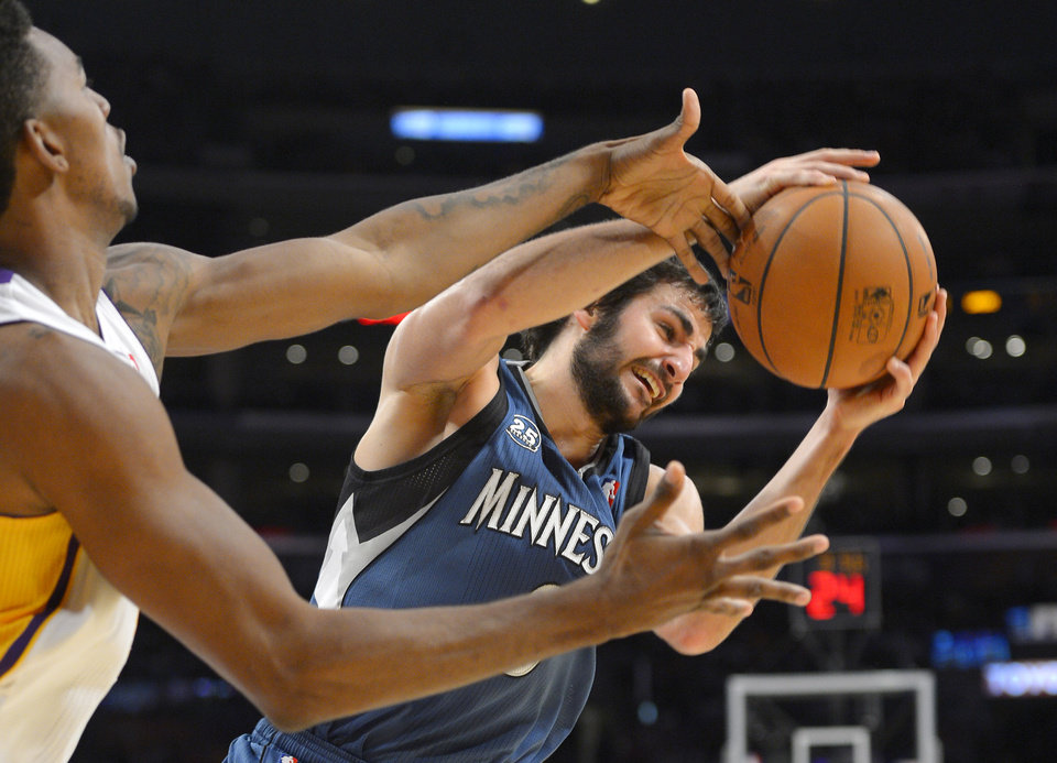 Photo - Minnesota Timberwolves guard Ricky Rubio, right, of Spain, grabs a rebound away from Los Angeles Lakers forward Nick Young during the first half of an NBA basketball game, Sunday, Nov. 10, 2013, in Los Angeles. (AP Photo/Mark J. Terrill)